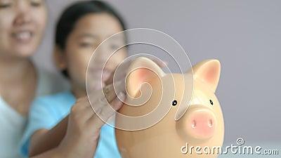 Moeder en klein Aziatisch meisje dat munt in de metafoor van de spaarpot gooit en geld bespaart voor een betere toekomst, kies ee stock video