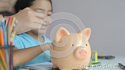 Moeder en klein Aziatisch meisje dat munt in de metafoor van de spaarpot gooit en geld bespaart voor een betere toekomst, kies ee stock videobeelden