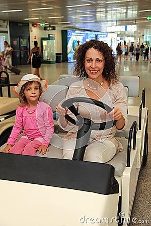 Moeder en weinig dochter die op elektrische auto berijden