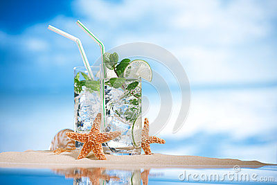 Mojito cocktail on beach sand and tropical seascape
