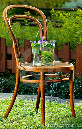 Mojito cocktail built around old chair on garden
