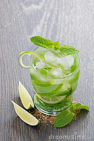 Mojito cocktail with lime and mint on wooden table, vertical