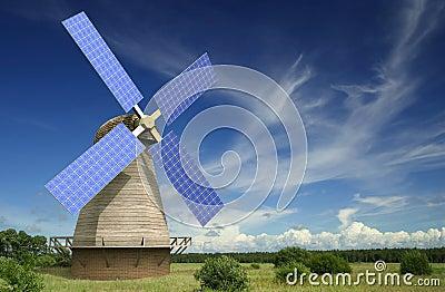 Molino de viento viejo con los paneles solares en sus alas
