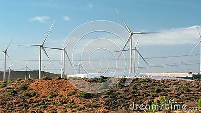 Molinos de viento girando para generar electricidad, colinas onduladas en el fondo El concepto de conservación del medio ambiente almacen de metraje de vídeo