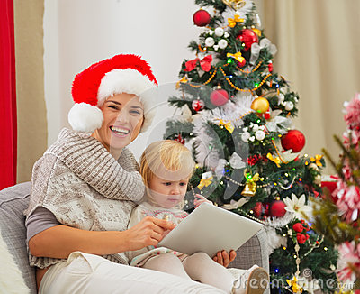 Mom and baby using tablet PC near Christmas tree