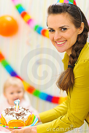 Mom carries birthday cake to baby