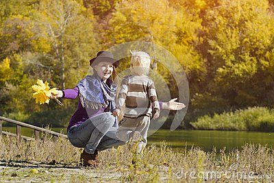 Mom catches running son. Autumn, a sunny day. River bank Stock Photo