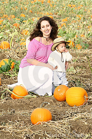 Mom and Child Sitting in a Pumpkin Patch