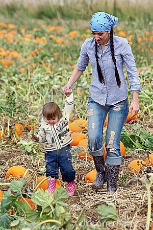 Mom and Child Walking in a Pumpkin Patch