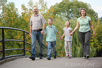 Mom, dad, son and daughter is walking on bridge