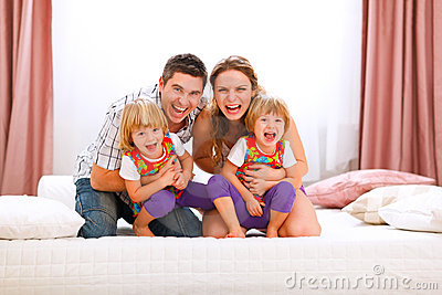 Mom dad and twins daughters having fun time