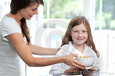 Mom feeding daughter breakfast cereal