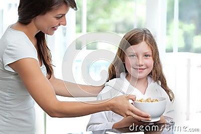 Mom feeding daughter breakfast cereal