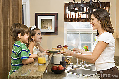 Mom giving kids breakfast.