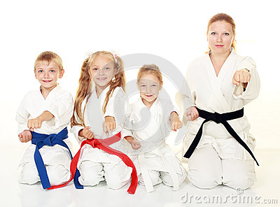 Mom with her daughter and a boy sitting with his sister in a ritual pose karate and beat his fist