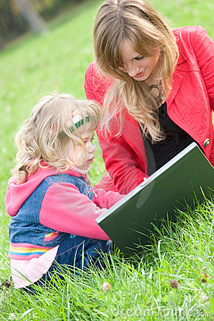 Mom and little daughter with laptop outdoor