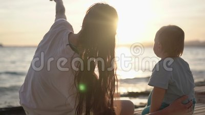 Mom shows to the baby something in the sky, being near the sea in slow motion. Mom shows to the baby something in the sky, They sit near the sea at sunset stock video footage