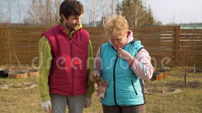Mom and son in the garden in spring. Young adult son giving his senior mother a small spring flower. Mother hugging and kissing him. Mothers day, relations stock footage