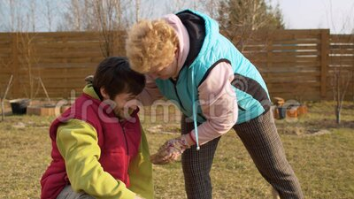 Mom and son in the garden in spring. Young adult son giving his senior mother a small spring flower. Mother hugging and kissing him. Mothers day, relations stock video footage