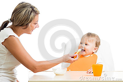 Mom spoon feeding her happy baby girl