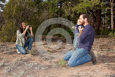 Mom taking a picture of son and dad