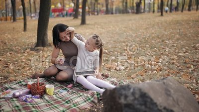 Mom teaches her daughter to write with chalk on a blackboard letters, the  alphabet  A young mother is having fun playing  Blond, drawing