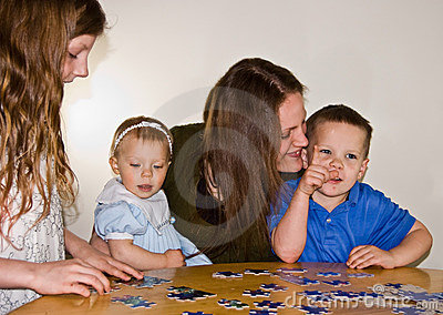 Mom and Three Kids Doing A Puzzle