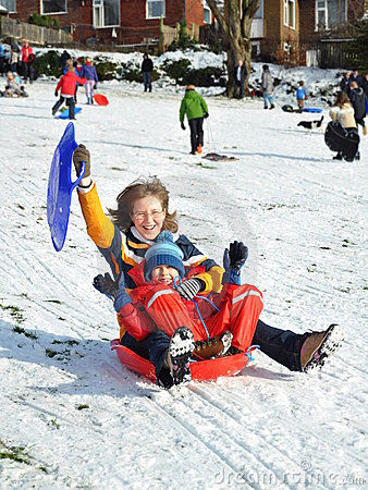 Momia e hijo en el trineo que resbala la colina nevosa, invierno