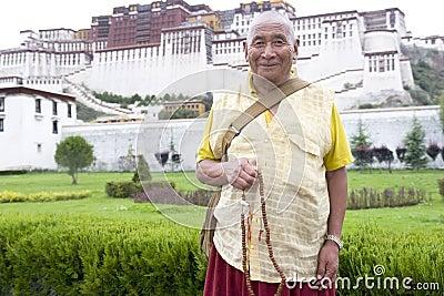 Monje tibetano delante del palacio de Potala Fotografía editorial
