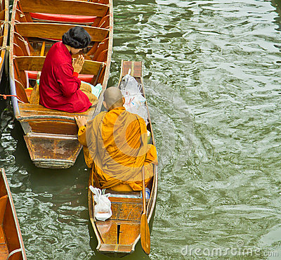 Monk on a boat at floating market, Thailand Editorial Photography