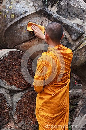 Monk is cleaning Buddha statue Editorial Image