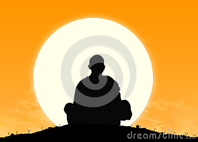 Monk in meditation at sunrise