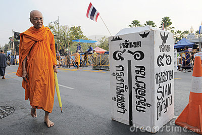 Monk passes a mock border at a Bangkok protest Editorial Photo