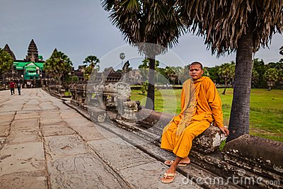Monk sits on walkway of Angkor Wat Temple Editorial Stock Photo