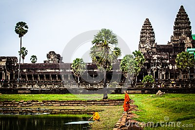 Monk stands on moat wall at Angkor Wat Temple Editorial Image