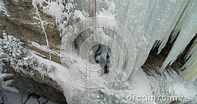 Montanhista de gelo que escala o penhasco congelado durante o inverno 4k video estoque