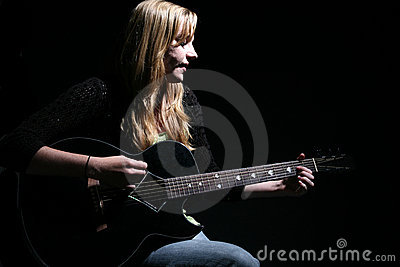 Moody woman playing guitar and singing