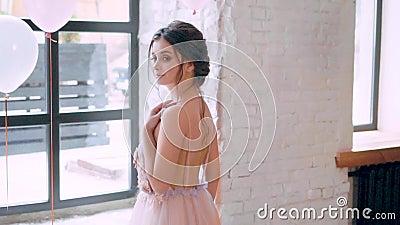 Mooi aantrekkelijk meisje in losse lichte kleding met open naakte rug, die zich bij reusachtig venster bevinden, die geheimzinnig stock footage