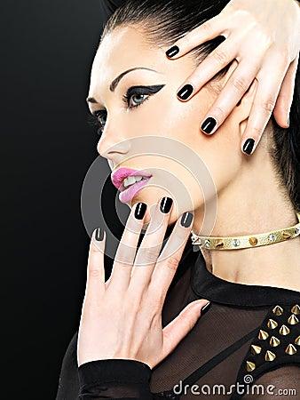 Het mooie gezicht van maniervrouw met zwarte spijkers en helder maakt