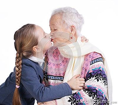 Mooi meisje die haar grootmoeder kussen