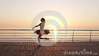 Mooi silhouet van ballerina in ballettutu en punt op dijk boven oceaan of overzees bij zonsopgang Jonge mooi stock videobeelden