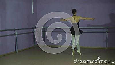 Mooie bevallige ballerine in de zwarte positie van het praktijk arabesque ballet in zaal stock footage