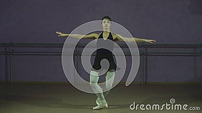 Mooie bevallige ballerine in de zwarte positie van het praktijk arabesque ballet in zaal stock videobeelden