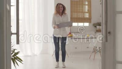 Mooie blanke meid die goed nieuws krijgt van de laptop en omhoog springt Betrouwbare jonge vrouw die online communiceert van stock video