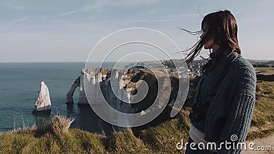 Mooie brunette vrouwelijke toerist met camera's langs de prachtige zeekust in Etretat met haar in de wind blazen stock videobeelden
