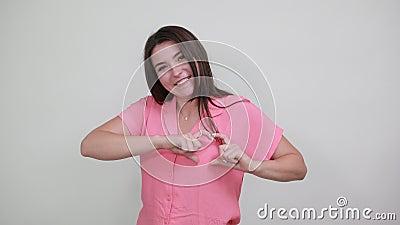 Mooie caucasiaanse jonge vrouw in een roze hemd die een vorm van hart aan het doen is, en er grappig uitziet stock footage