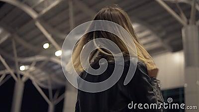 Mooie jonge vrouw buiten op de straat, die voor camera, het glimlachen stellen duisternis Lage hoeklengte stock video