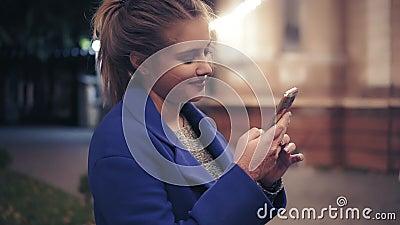 Mooie jonge vrouw die haar slimme telefoon met behulp van laat bij nacht in de stad Het aantrekkelijke meisje texting, die op Int stock video