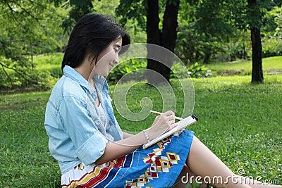 Mooie jonge vrouw die in openlucht in een park schrijft