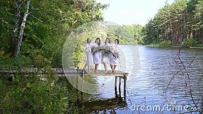 Mooie meisjes in volksjurken op houten pontons boven de rivier stock videobeelden